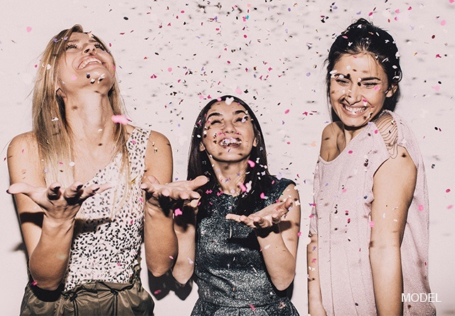 A group of woman smiling and holding out hands trying to catch confetti