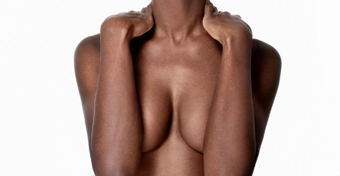 Woman covering breasts with arms