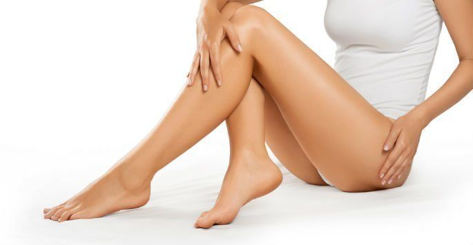 Woman looking at her legs considering laser hair removal