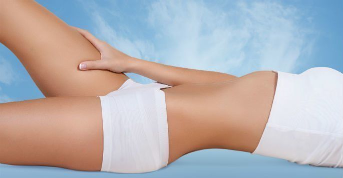 Woman lying down showing toned tummy