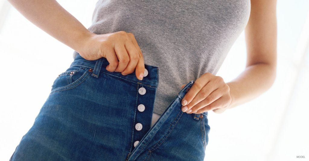 Woman getting dressed, concerned about stomach bulges