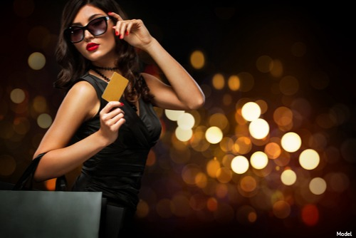 Model holding gold card wearing sunglasses
